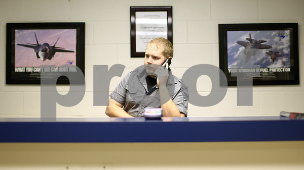 Kyle Bursaw – kbursaw@shawmedia.com<br /> <br /> Evan Webb, a 22-year-old line service technician, talks on the phone with an incoming chartered plane from Raleigh, N.C. at the DeKalb Taylor Municipal Airport on Monday, Dec. 3, 2012.