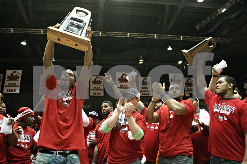 Rob Winner – rwinner@shawmedia.com<br /> <br /> Northern Illinois cornerback Rashaan Melvin (left) holds up the 2012 Mid-American Conference Championship trophy at a pep rally for the NIU football team during halftime of the men's basketball game at the Convocation Center in DeKalb, Ill., Wednesday, Dec. 5, 2012.