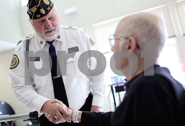 Kyle Bursaw – kbursaw@shawmedia.com<br /> <br /> Ken Andersen, who served in the army from 1961-3 shakes the hand of air force veteran John Vissering (right), a resident of the DeKalb County Rehab &<br /> Nursing Center, after Andersen was presented a quilt from the DeKalb County Quilters' Guild to Vissering on Friday, Dec. 7, 2012.