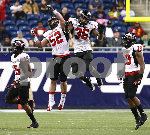 Kyle Bursaw – kbursaw@shawmedia.com<br /> <br /> Northern Illinois linebackers Michael Santacaterina (52) and Tyrone Clark (36) celebrate an interception by teammate Dechane Durante (not pictured) in the second quarter. The Northern Illinois University Huskies defeated the Kent State Golden Flashes 44-37 in the MAC conference championship game at Ford Field in Detroit, Mich. on Friday, Nov. 30, 2012.