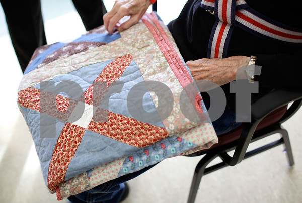 Kyle Bursaw – kbursaw@shawmedia.com<br /> <br /> John Vissering (right), an air force veteran and resident of the DeKalb County Rehab & Nursing Center holds the quilt he was recently given by the DeKalb County Quilters' Guild in his lap on Friday, Dec. 7, 2012.