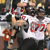 Kyle Bursaw – kbursaw@shawmedia.com<br /> <br /> Northern Illinois tight end Jason Schepler (87) hoists up quarterback Jordan Lynch (6) following Lynch's touchdown in the second overtime period. The Huskies defeated Kent State 44-37 in the MAC conference championship game at Ford Field in Detroit, Mich. on Friday, Nov. 30, 2012