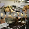 Rob Winner – rwinner@shawmedia.com<br /> <br /> Volunteers Destiny Johnson (left) and Brooke Wilson prepare a batch of brownies in the Feed'em Soup kitchen in DeKalb Thursday night. Feed'em Soup is expanding their services by offering Feed'em - After Dark on the weekends.