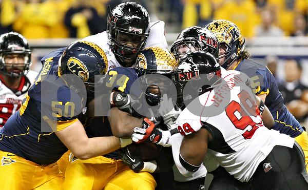 Kyle Bursaw – kbursaw@shawmedia.com<br /> <br /> The Northern Illinois defensive tackle Nabal Jefferson (99) assists on a tackle of Kent State running back Trayion Durham (34) during the MAC Championship game at Ford Field in Detroit, Friday, Nov. 30, 2012.