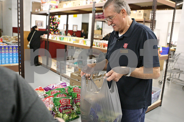 Rob Winner – rwinner@shawmedia.com<br /> <br /> Gary Billings, food pantry coordinator, holds a bad for a client at the Salvation Army in DeKalb, Ill., Thursday, Dec. 13, 2012.