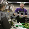 Rob Winner – rwinner@shawmedia.com<br /> <br /> Volunteer Destiny Johnson (left) talks with executive chef Alex Smith in the kitchen of Feed'em Soup in DeKalb Thursday night as Smith breaks up lettuce while making Ahuaca Verde Chicken Sliders. Feed'em Soup is expanding their services by offering Feed'em - After Dark on the weekends.