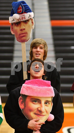 Kyle Bursaw – kbursaw@shawmedia.com<br /> <br /> DeKalb fans Justin Barker (front) and Bret Thomas sing the national anthem while holding enlarged photographs of players Andre Harris (top) and Jordan Rossdeutcher (bottom) before the Barbs game against Winnebago in the Chuck Dayton Holiday Tournament in DeKalb, Ill. on Friday, Dec. 21, 2012.