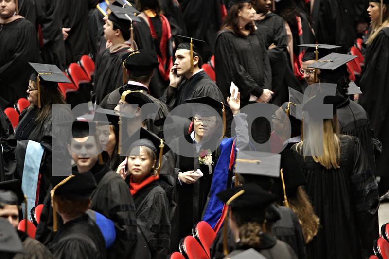 Rob Winner – rwinner@shawmedia.com<br /> <br /> A graduate waves to the crowd as the Northern Illinois University graduate school commencement ceremony begins inside the Convocation Center in DeKalb, Ill, Saturday, Dec. 15, 2012.