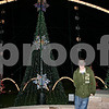 Nick Andreas poses with the Christmas light display he set up in the backyard of his DeKalb home. The lights are programmed to shine on and off to popular and holiday music that plays over a small radio transmitter Andreas has.