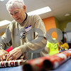 Kyle Bursaw – kbursaw@shawmedia.com<br /> <br /> Sycamore resident Phyllis Roush wraps up toys and clothes being distributed to families for the holidays at the Salvation Army in DeKalb, Ill. on Tuesday, Dec. 18, 2012.