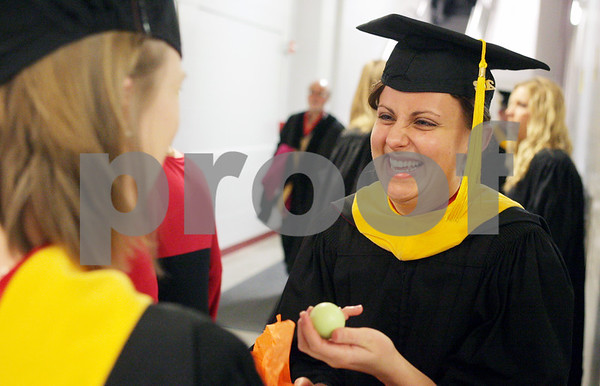Rob Winner – rwinner@shawmedia.com<br /> <br /> Jessica Harris (right) reacts after receiving a gift of lip balm from Karen Ruhl before Saturday's graduate school commencement ceremony inside the Convocation Center at Northern Illinois University in DeKalb.<br /> <br /> Saturday, Dec. 15, 2012