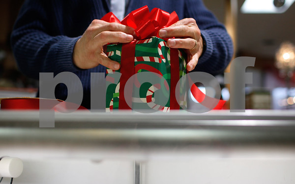 Kyle Bursaw – kbursaw@shawmedia.com<br /> <br /> Rich Para, co-owner of Sweet Earth ties a bow into a gift he wrapped for a customer in Sycamore, Ill. on Tuesday, Dec. 18, 2012.