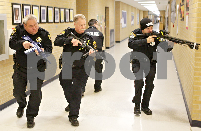"""Rob Winner – rwinner@shawmedia.com<br /> <br /> Kirkland police officers including Sgt. Paul Lindstrom (from left to right), Alton E. Parker, Jr., Travis Coburn, and Tony Miller maneuver around the corner of a hallway while participating in a Rapid Response training drill at Hiawatha Elementary School in Kirkland, Ill., Saturday, Dec. 15, 2012. Eight members of the Kirkland Police Department participated in the drills which began at 8 a.m. and concluded at 4 p.m. Training instructor Joe Drought, Chief at the Rock Valley College Police Department, said the one-day course is designed to """"teach officers to make an immediate response to an active shooter or ongoing threats to human life."""" <br /> <br /> ***Coburn has his back turned.***"""