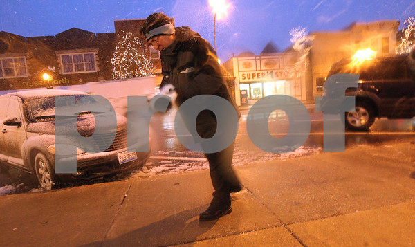 Kyle Bursaw – kbursaw@shawmedia.com<br /> <br /> Ken Elliott, co-owner of Made Just For You Gifts in Sycamore, tosses down some salt after shoveling outside of his store on Thursday, Dec. 20, 2012.