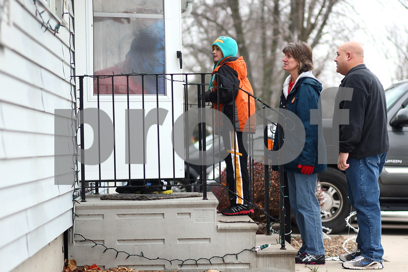Kyle Bursaw – kbursaw@shawmedia.com<br /> <br /> The Kozumplik family (from left) Zak, Rik, Cindy and Brian deliver a bag of gifts from Goodfellows to a family in DeKalb, Ill. on Monday, Dec. 24, 2012.