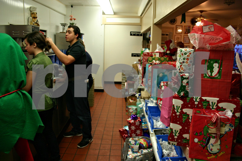 Jeff Engelhardt – jengelhardt@shawmedia.com<br /> Flippin Eggs employee Jeff McMaster works with volunteers behind a wall of gifts in the kitchen during the diner's annual free Christmas community meal event Sunday.