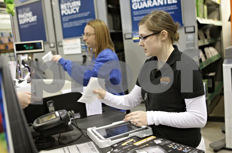 Rob Winner – rwinner@shawmedia.com<br /> <br /> Customer service agent Kellie Ratfield (front) is handed a receipt for a returned tablet case at Best Buy in DeKalb, Ill., Wednesday, Dec. 26, 2012.