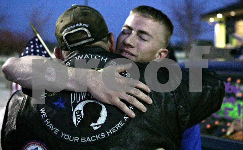 Rob Winner – rwinner@shawmedia.com<br /> <br /> Army Spc. Andrew Shores (right) is welcomed home by Warriors Watch Rider Russ Miller, of Burbank, outside First State Bank in Waterman before being escorted to the home of his fiancé in Shabbona, Ill., Saturday, Dec. 22, 2012. Shores, a 2008 Indian Creek High School graduate, had been serving in Afghanistan since March of this year.