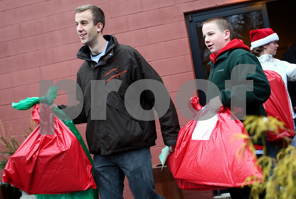 Kyle Bursaw – kbursaw@shawmedia.com<br /> <br /> Ryan Swartzendruber, 21 and his brother Brett, 13 (at right), both volunteering with Goodfellows, bring a handful of gift bags out of Blumen Gardens to deliver to families on Monday, Dec. 24, 2012.