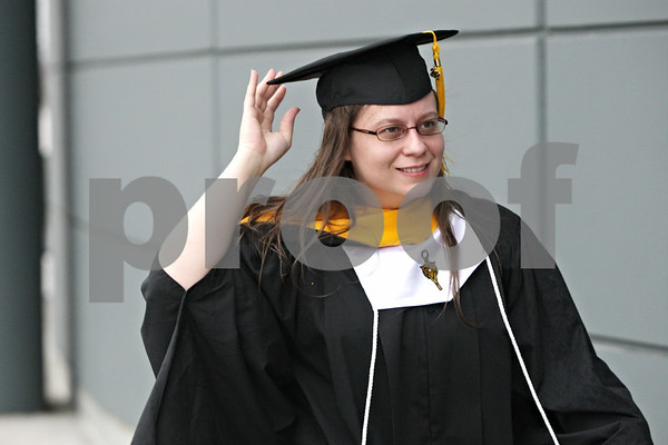 Rob Winner – rwinner@shawmedia.com<br /> <br /> Master of Science graduate Tricia Fremouw tries to keep dry before entering the Convocation Center in DeKalb for Saturday's Northern Illinois University commencement ceremony.<br /> <br /> Saturday, Dec. 15, 2012