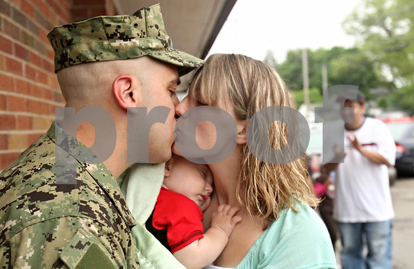 Rob Winner – rwinner@shawmedia.com<br /> <br /> Navy GSE3(SW) Justin Cano of DeKalb kisses his girlfriend, Kayla Bishop, as she holds her son, Drake Bishop, 8-months-old, upon arrival at Sullivan's Tavern Saturday for a welcome home celebration. Cano was escorted by a DeKalb fire engine followed by a group Warriors' Watch Riders, family and friends.