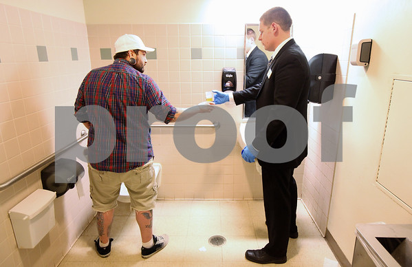 Kyle Bursaw – kbursaw@shawmedia.com<br /> <br /> Drug Court Probation Officer Mike Douglas accepts a urine sample from Matt Jordan in a bathroom at the DeKalb County Courthouse on Friday, March 16, 2012 after being in drug court. Jordan also has to call in every day before 8:30 a.m. throughout the duration of his time in drug court to see if he has to go to the courthouse for a random drug test.