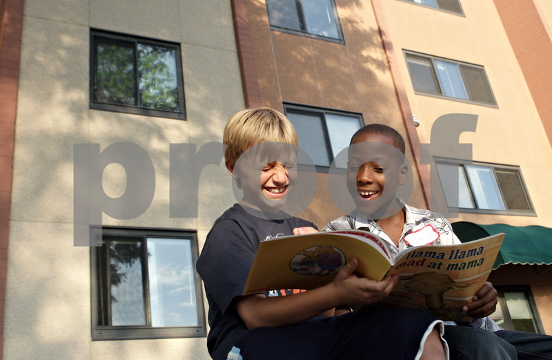 Rob Winner – rwinner@shawmedia.com<br /> <br /> William Moon (left), 9, and Kenneth Weeks, 8, take turns reading a book outside Gideon Court Apartments in DeKalb Tuesday evening. The two were participating in a free summer reading vacation program presented by Neighbors' House.