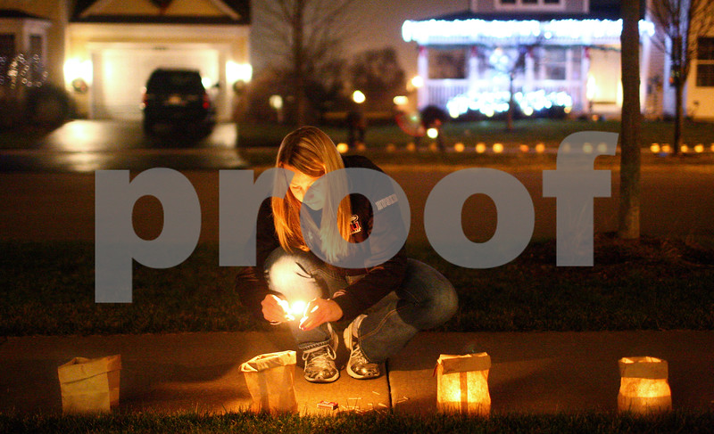 Kyle Bursaw – kbursaw@shawmedia.com<br /> <br /> Kalie Kuhl lights one of 27 luminarias, one to represent each of the victims in Newton, Conn., on the sidewalk outside her home in the Reston Ponds neighborhood in Sycamore, Ill on Tuesday, Dec. 18, 2012. Kuhl and another neighbor, Kristin Miller, helped get the word out and distribute supplies for others in the neighborhood to also light luminaries, she estimates about 30 of the neighborhoods homes took part.