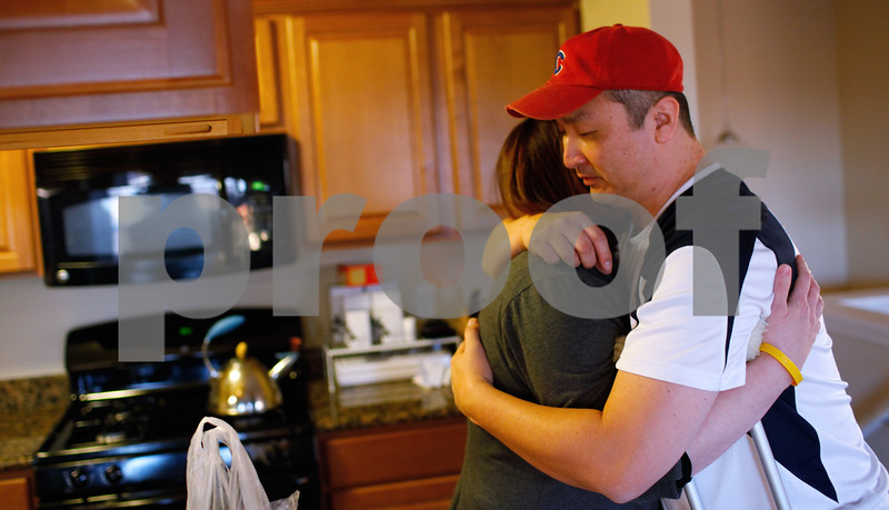 Kyle Bursaw – kbursaw@shawmedia.com<br /> <br /> Ginger McQueen hugs her husband of four years, John Hahn, after he gave her a Kindle Fire HD in their Sycamore home on Wednesday, Dec. 12, 2012. Hahn said he wanted to get her something because she has done a number of things to help him while he is recovering from a ruptured brain aneurysm, including quitting her job and taking care of him in a number of ways like helping him put on socks and shoes. Hahn is slated to return to teaching art at three DeKalb elementary schools at the end of January.