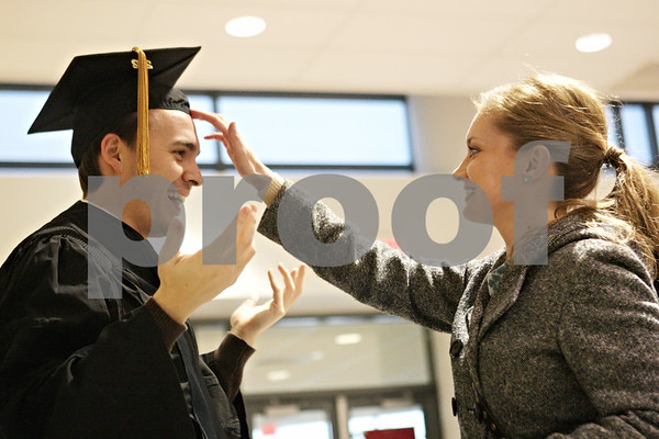 Rob Winner – rwinner@shawmedia.com<br /> <br /> Northern Illinois University alumni Jenny Jakob (right) helps her fiancé, Neil Wright, with his cap inside the Convocation Center in DeKalb before Saturday's commencement ceremony.<br /> <br /> Saturday, Dec. 15, 2012