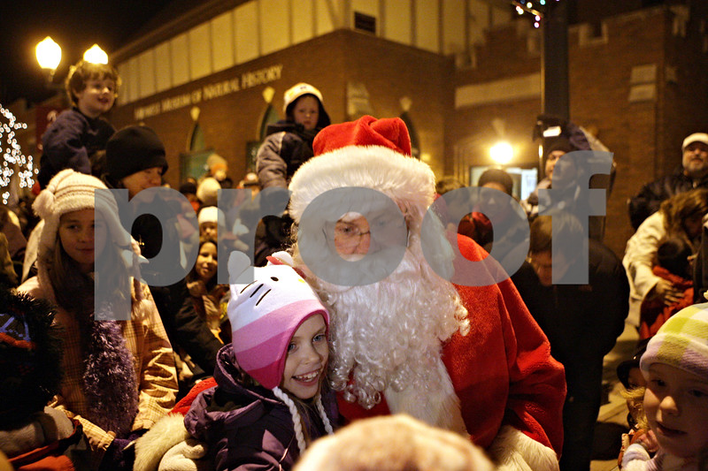 Rob Winner – rwinner@shawmedia.com<br /> <br /> Natalie Snyder, 8, of Sycamore, poses for a photograph with Santa Claus after his arrival outside the Midwest Musuem of Natural History in downtown Sycamore, Ill., Friday, Dec. 7, 2012.