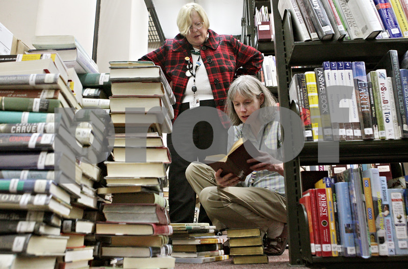 Rob Winner – rwinner@shawmedia.com<br /> <br /> Library director Dee Coover (left) and Teresa Iversen, head of reference, look over books to decide which ones will stay and go to make room for office space on the third floor of the DeKalb Public Library on Wednesday, Dec. 26, 2012. The Illinois Public Library released $8.5 million to give the DeKalb library toward its construction and renovation plan, so long as library leaders can raise local matching funds by June 30.