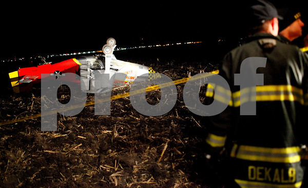 Kyle Bursaw – kbursaw@shawmedia.com<br /> <br /> Firefighter paramedics work at the scene of the crash of a small aircraft in an open field south of Route 38 between DeKalb and Cortland. The aircraft was being flown by 62-year-old Sycamore resident James L. Auman on Tuesday, Dec. 11, 2012.