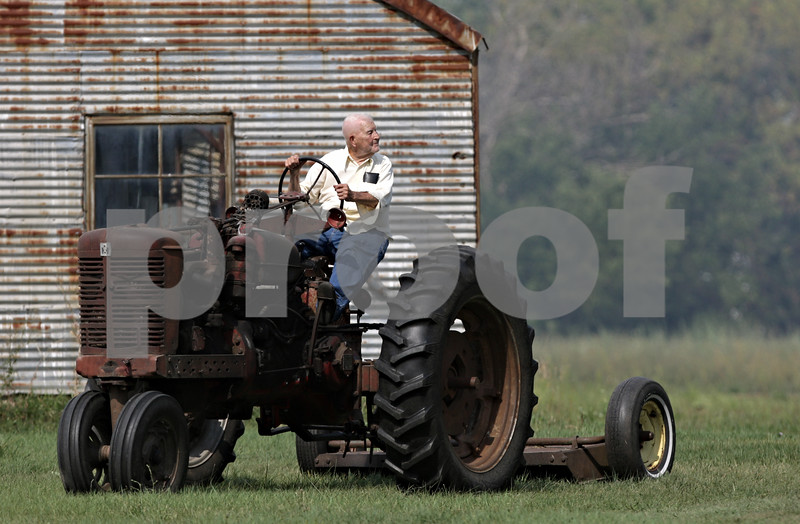"""Rob Winner – rwinner@shawmedia.com<br /> <br /> 88-year-old Lloyd Collier looks back to his barn while moving his tractor from potential damage as firefighters control a fire on Collier's property located off of West Lincoln Highway in DeKalb, Ill., Saturday, Aug. 25, 2012. """"I don't accept losing physical things as a catastrophe,"""" said Collier as he sat in his tractor looking toward his home."""