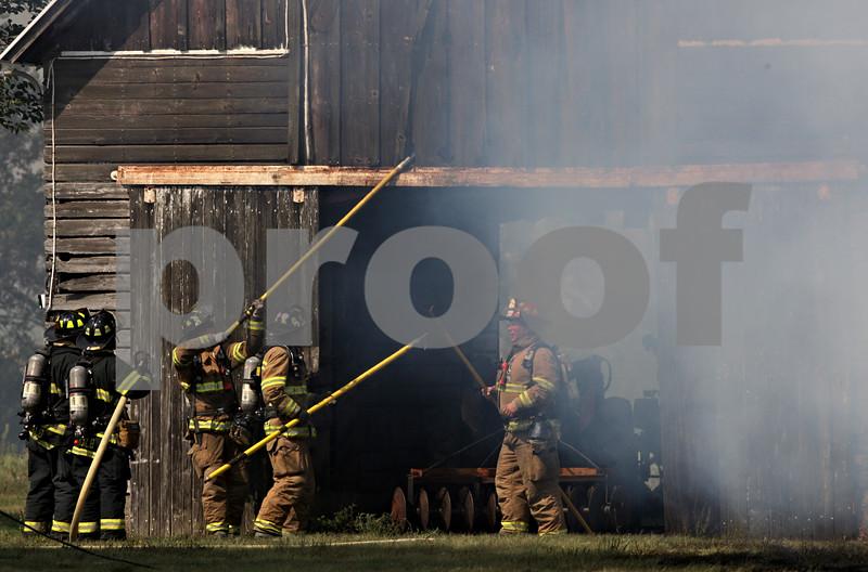 Rob Winner – rwinner@shawmedia.com<br /> <br /> Firefighters inspect a corn crib located on Lloyd Collier's property on West Lincoln Highway in DeKalb, Ill., Saturday, Aug. 25, 2012.