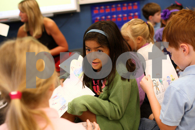 Kyle Bursaw – kbursaw@shawmedia.com<br /> <br /> Maggie Penate-Lopez chats with a classmate between classmates drawings about things they did over the summer in Kelly Wright's first grade class at North Grove Elementary on Wednesday, Aug. 22, 2012.