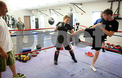 Kyle Bursaw – kbursaw@shawmedia.com  Danika practices some of her countering techniques against Nate Beach, 20, as Pat White, a boxing and Muay Thai coach (far left), and Sean Thibault (back left) look on at the Academy of Human Performance in Aurora, Ill. on Tuesday, July 10, 2012.