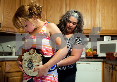 Kyle Bursaw – kbursaw@shawmedia.com  Danika's mother Rena helps fasten her championship belt from her victory in the IKF tournament in Orlando. Danika decided she wanted to wear it and her silver medal from a grappling competition in San Diego to show off to her sister's friends while having a party celebrating her victories on Tuesday, Aug. 28, 2012.