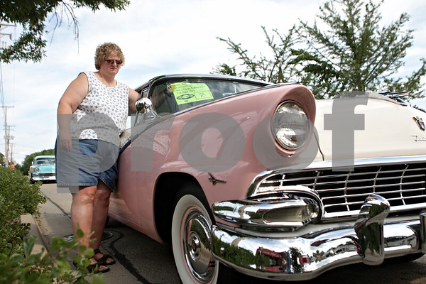 Rob Winner – rwinner@shawmedia.com<br /> <br /> Jeanne Chybik of Maple Park hangs an information card for her 1956 Ford Victorian during the Turning Back Time Weekend Cruise Night in Sycamore, Ill., Saturday, July 28, 2012.
