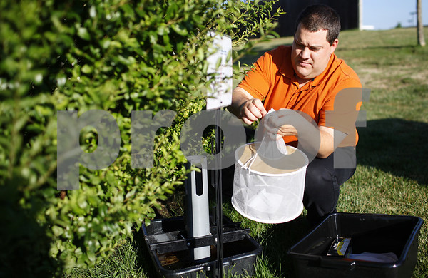 Kyle Bursaw – kbursaw@shawmedia.com<br /> <br /> Greg Maurice, the director of environmental health with the DeKalb County Health Department, changes out a CDC Gravid trap in DeKalb, which catches mosquitos on Tuesday, July 31, 2012.