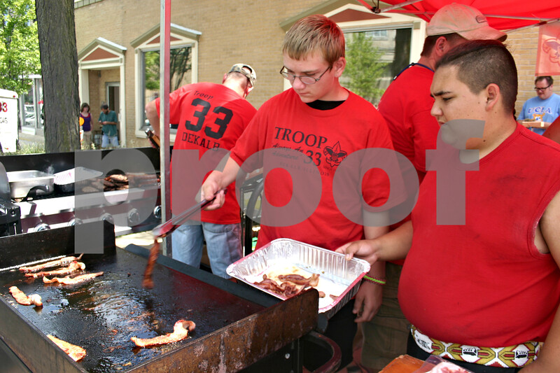 Boy Scout Troop 33 members Brandon Tolliver, 16, right, and Matt Moon, 14, make bacon during BaconPalooza Saturday, which was part of Kishwaukee Fest.<br /> <br /> By Nicole Weskerna - nweskerna@shawmedia.com
