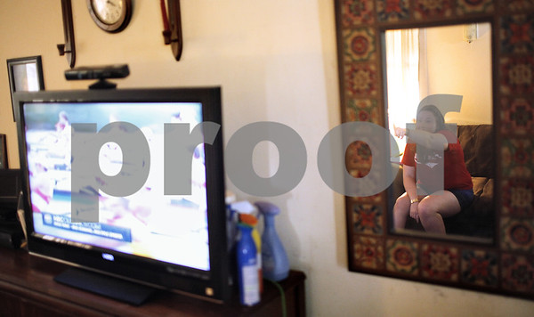 Kyle Bursaw – kbursaw@shawmedia.com<br /> <br /> Elizabeth Becker, 22, reacts while watching the Olympic rowing finals, an event her friends Grant and Ross James were competing in, from her DeKalb home on Wednesday, Aug. 1, 2012. The former DeKalb High School students took fourth place in the race.