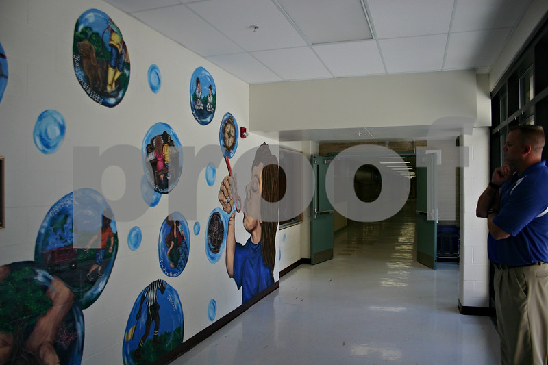 Jeff Engelhardt – jengelhardt@shawmedia.com<br /> West Elementary Principal Bradley Barnhardt looks at the mural art teacher Heather Havlicek created during the summer. The mural promotes the school's core values.