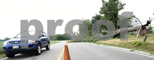 Kyle Bursaw – kbursaw@shawmedia.com  A portion of Airport Road was down to one lane as a fallen tree spilled into the road in Sycamore, Ill. on Tuesday, July 24, 2012.