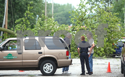 Kyle Bursaw – kbursaw@shawmedia.com  Vinnie Laudicina (center) and Lieutenant Paul Rubeck (right), both from the Sycamore Fire Department, talk with a property owner while stationed to keep people away from the downed power lines on the 200 block of North Cross Street in Sycamore, Ill. on Tuesday, July 24, 2012.