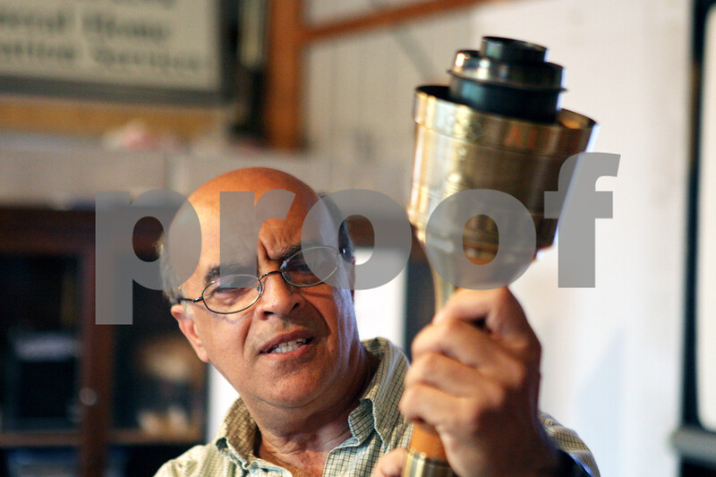 Rob Winner – rwinner@shawmedia.com<br /> <br /> While giving a presentation at the Sycamore History Museum on Wednesday evening, Abed Zantout of Sycamore holds up an Olympic torch which he helped engineer while working for Turner Industries in 1984.