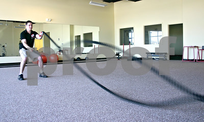 Chris Jarvis, owner of Sycamore Elite Fitness, demonstrates how to use battle ropes in the gym he opened in early June.  By Nicole Weskerna - nweskerna@shawmedia.com