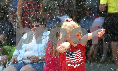 Kyle Bursaw – kbursaw@shawmedia.com  Meghan Rush, 8, reacts to a firefighter raining some water down on the crowd during Kirkland's Fourth of July parade.  Wednesday, July 4, 2012