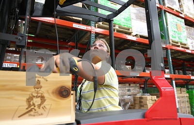Kyle Bursaw – kbursaw@shawmedia.com  Shannon Albright, warehouse supervisor at 3M's Macom Drive location in DeKalb, grabs her barcode scanner out of a convenience tray attached to her forklift on Wednesday, June 27, 2012. The tray was made by DeKalb High School students.