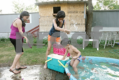 Rob Winner – rwinner@shawmedia.com  Andrea Sanchez (left), 20, and her sister Brenda Sanchez, 12, play with Andrea's son David Alarcon, 3, outside their home at Evergreen Village in Sycamore Thursday evening.
